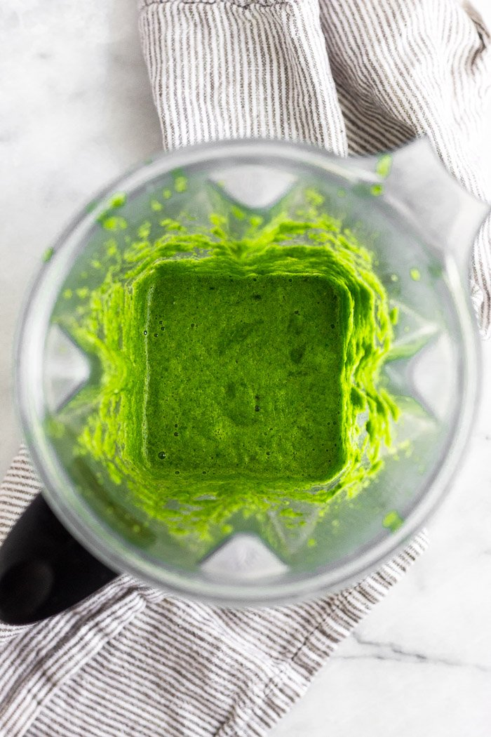 Blender filled with a green puree of herbs, peppers, and broth.