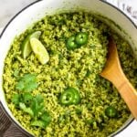 Large dutch oven filled with arroz verde topped with limes, jalapenos, and cilantro. There is a wooden spoon coming out of the pan. The pan is sitting on a towel with a bowl of cilantro and limes next to it.