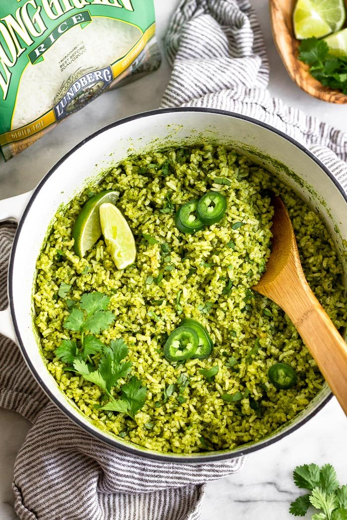 Large stock pot filled with green rice topped with jalapeños, limes wedges, and cilantro. Around it is a bag of white rice, a plate of herbs and lime, and a striped linen.