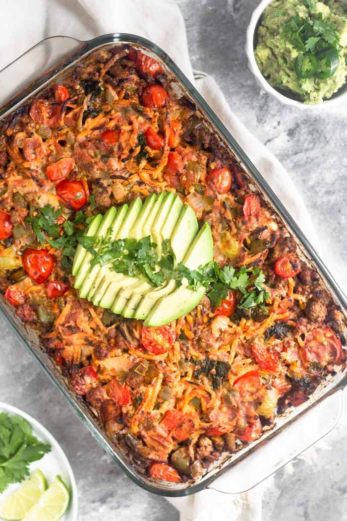 Beef taco casserole topped with slice avocado and cilantro.
