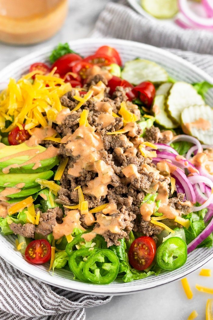 Cheeseburger salad with lettuce, ground beef, tomato, cheese, avocado, special sauce, pickles, jalapeños, onions, and special sauce dressing.