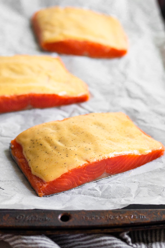 Baking sheet lined with parchment paper with 3 raw salmon filets topped with chipotle mayo.