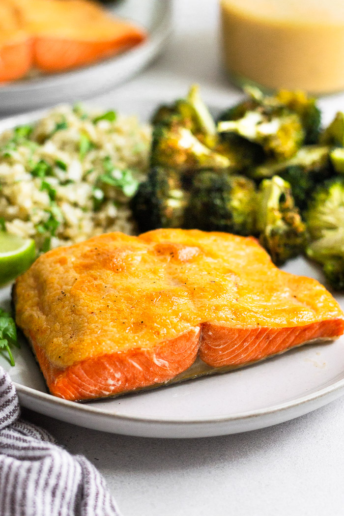 Plate of air fryer salmon that is covered in chipotle mayo. Next to it is roasted broccoli and cauliflower rice. Behind it is the jar of mayo and another plate of salmon.