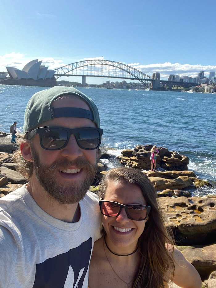 Husband and wife taking a selfie with the Sydney Opera House and bridge behind them.