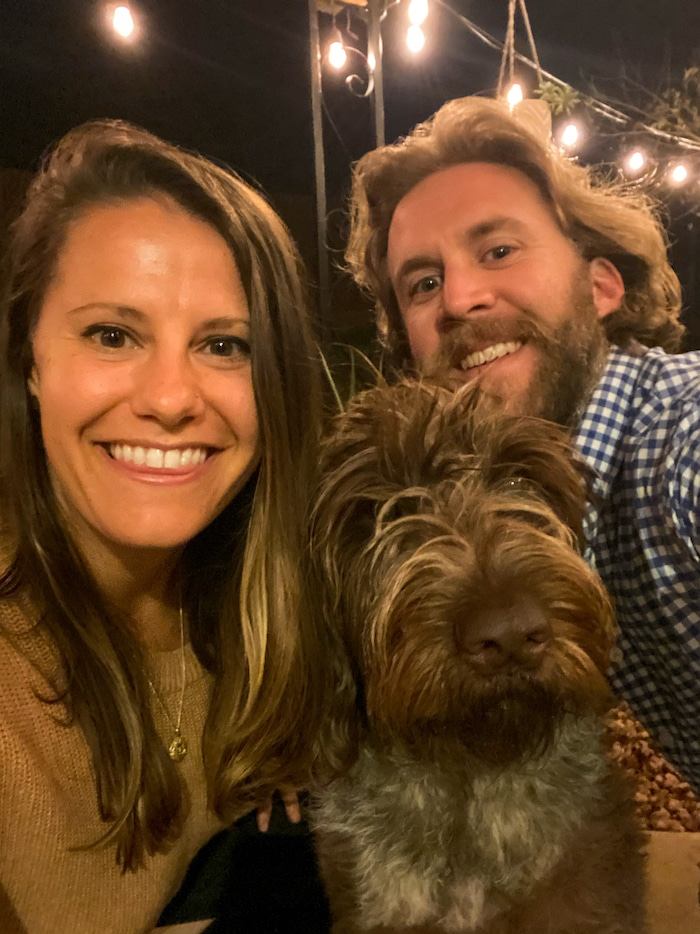 Woman, man, and a dog taking a selfie at night with lights on in the background.
