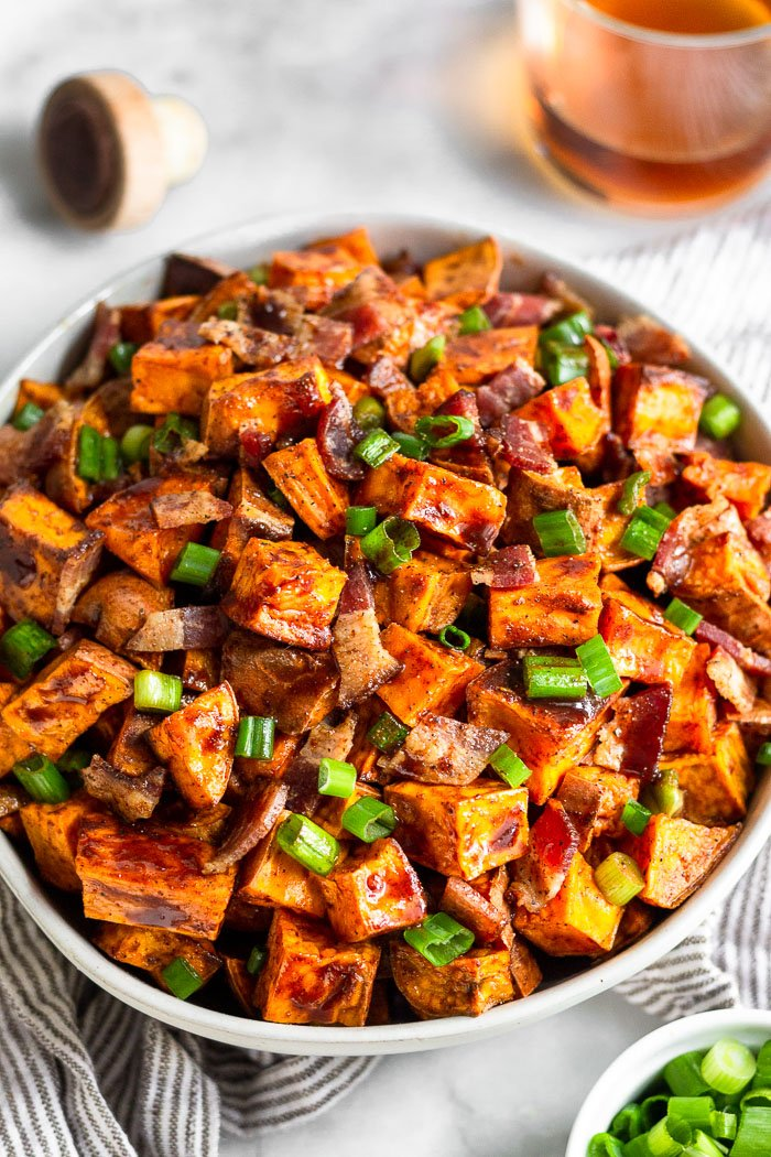 A bowl of glazed sweet potatoes with a glass of whiskey, a bowl of green onion, and a cork to a bottle around it.