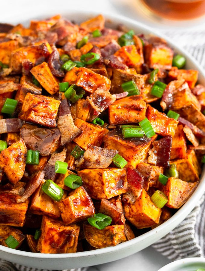 Bowl of glazed sweet potatoes topped with bacon and green onions. Next to is a bowl of green onions and behind it a glass of whiskey.