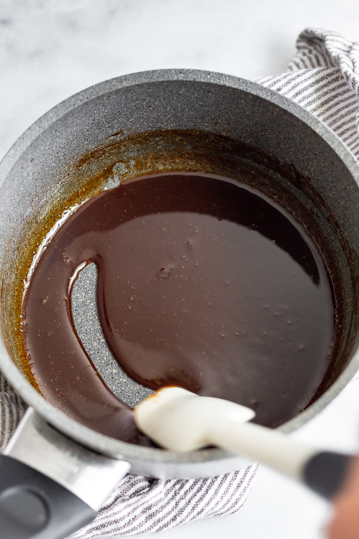 Whiskey glaze in a small sauce pan with a spatula running through it leaving a clean line.