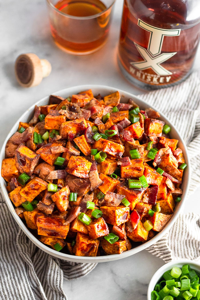 Bowl of whiskey glazed sweet potatoes topped with bacon and green onion. The bowl is sitting on a striped towel with a bowl of green onions, bottle of whiskey, a cup of whiskey, and the bottle's cork next to it.