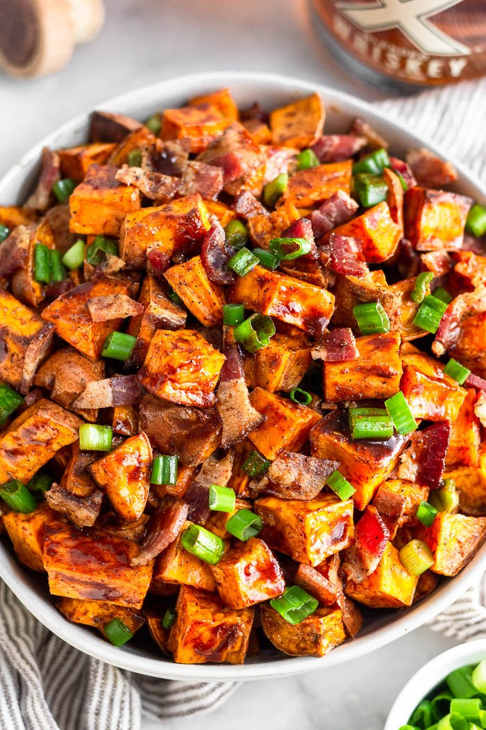 Bowl of whiskey glazed sweet potatoes topped with bacon and chopped green onions. It is sitting on a striped towel with a bowl of green onions and a bottle whiskey around it.