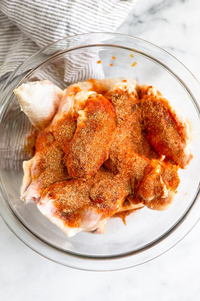Bowl of raw chicken wings covered in spices.