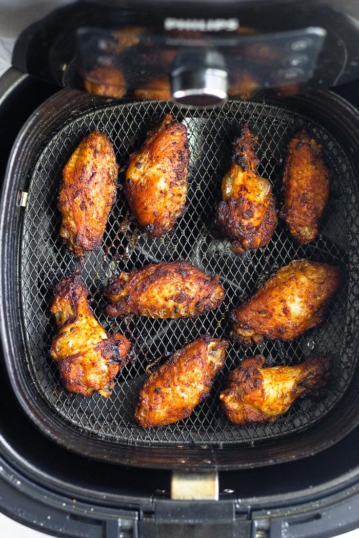Air fryer chicken wings in an air fryer basket.