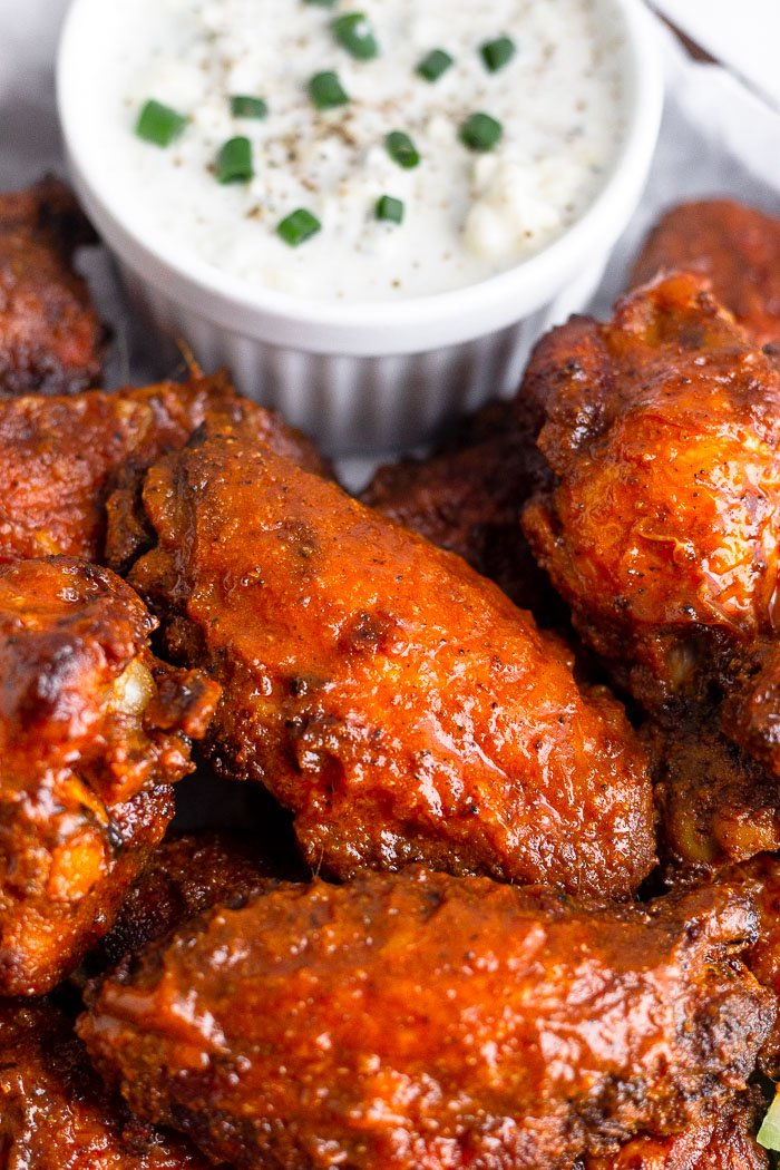Close up of an air fryer chicken wing surrounded by other wings and a small bowl of blue cheese dressing behind them.
