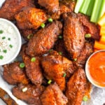 Overhead shot of a pile of air fryer buffalo wings on a baking sheet garnished with chopped green onions. Next to them in are two bowls of blue cheese dressing and hot sauce with celery and carrots on the side.