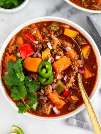 Bowl of bison chili with butter squash topped with jalapenos, cilantro, and red onion. A spoon is coming out of the bowl and around is is another bowl, a bowl of cilantro, and lime wedges.