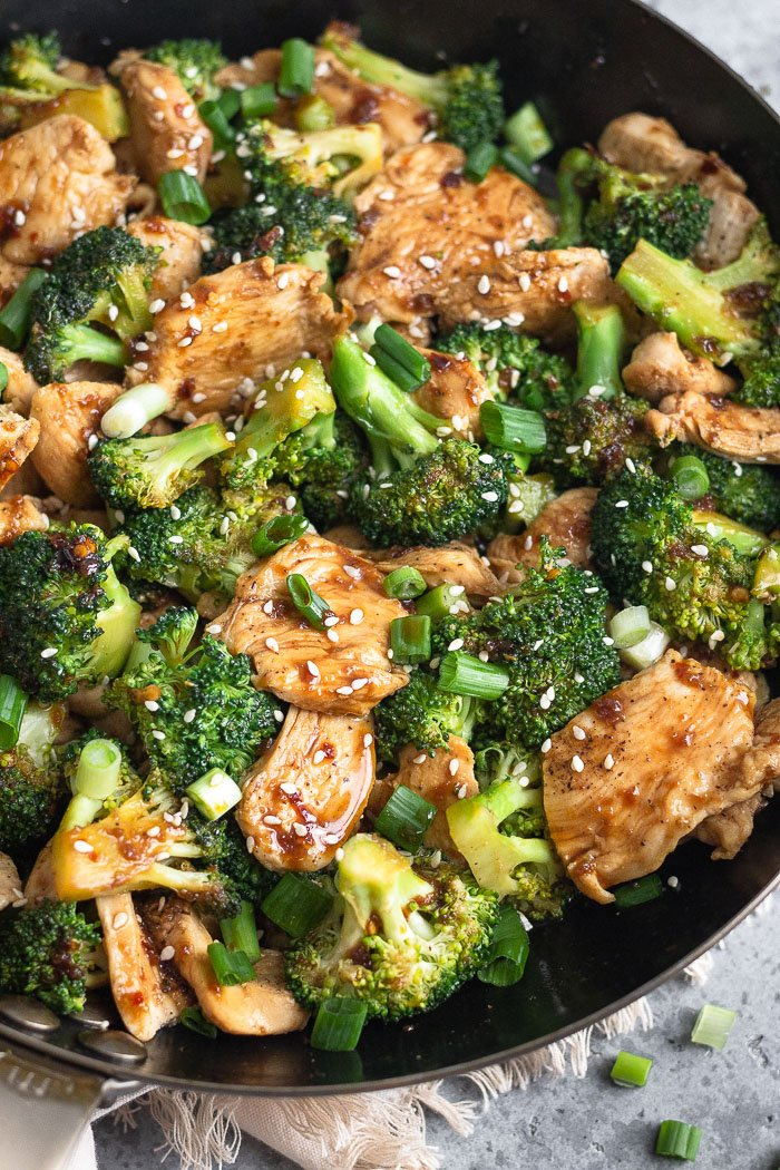 Close up of a large saute pan filled with healthy chicken and broccoli stir fry topped with sesame seeds and chopped green onions.