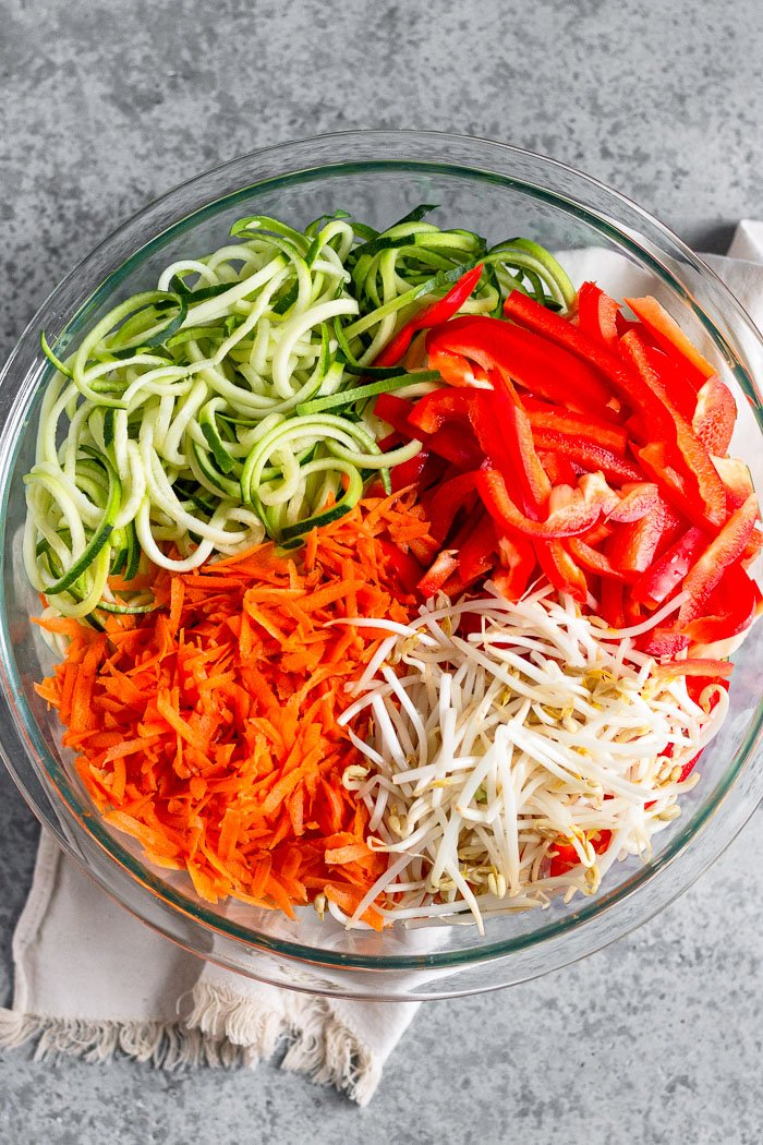 Large glass bowl of zucchini noodles, chopped bell peppers, bean sprouts, and shredded carrots.