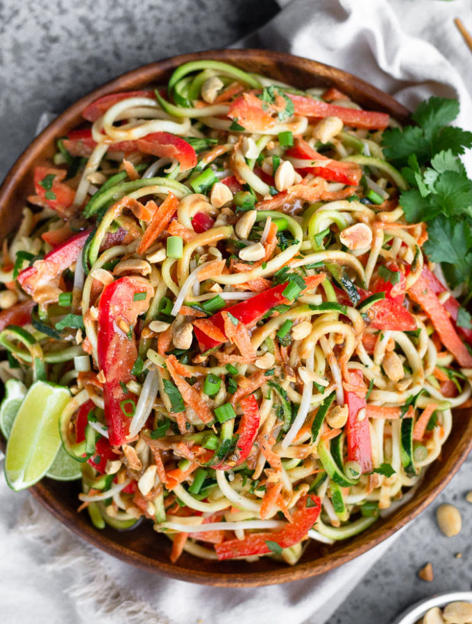 Plate filled with raw pad thai salad made from zucchini noodles, carrots, and bell peppers. It is garnished with lime wedges, cilantro, and peanuts. Next to it is a bowl of peanuts, white linen, and half a lime.