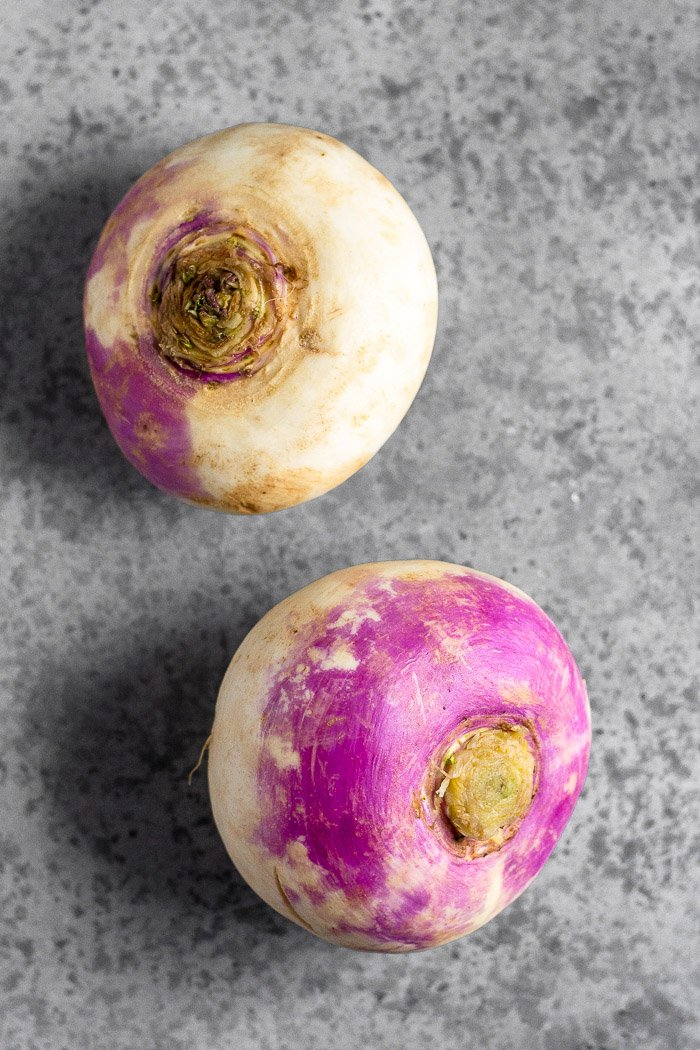 Two large turnips on a grey surface.