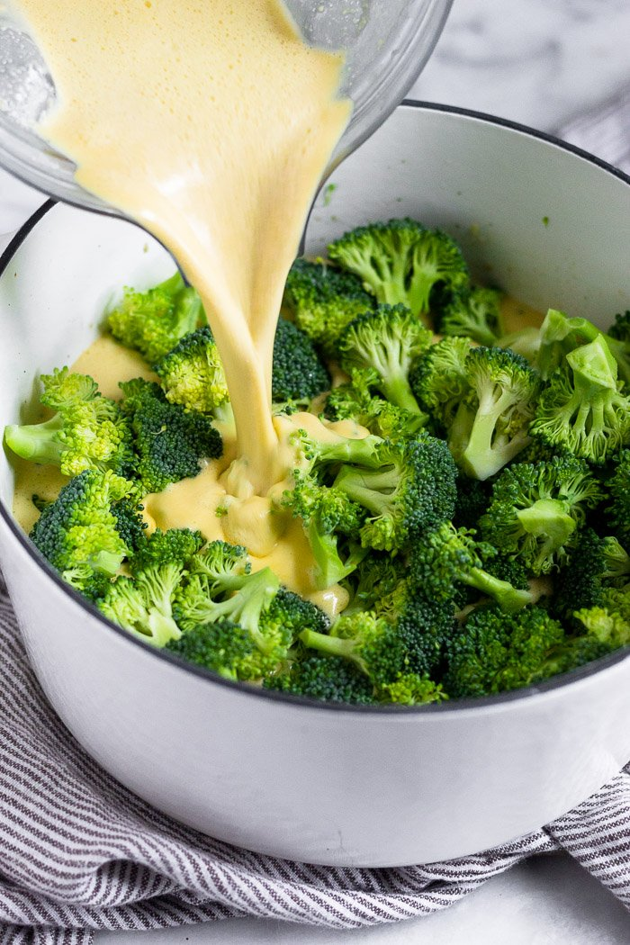 Large white dutch oven filled with fresh broccoli and a vegan cheesy broth being poured over it.