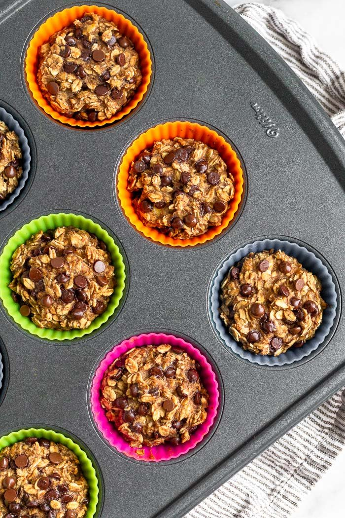 Muffin tin filled with baked oatmeal cups with chocolate chips.