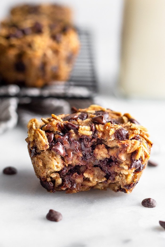 Healthy oatmeal chocolate chip muffin with a bite taken out of it. Behind it is a rack of more muffins and a jar of milk.