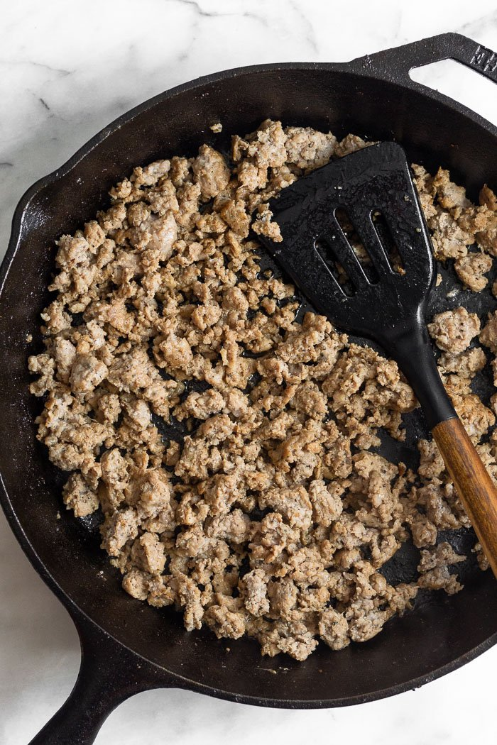 Cast iron skillet filled with cooked ground sausage with a spatula in it.