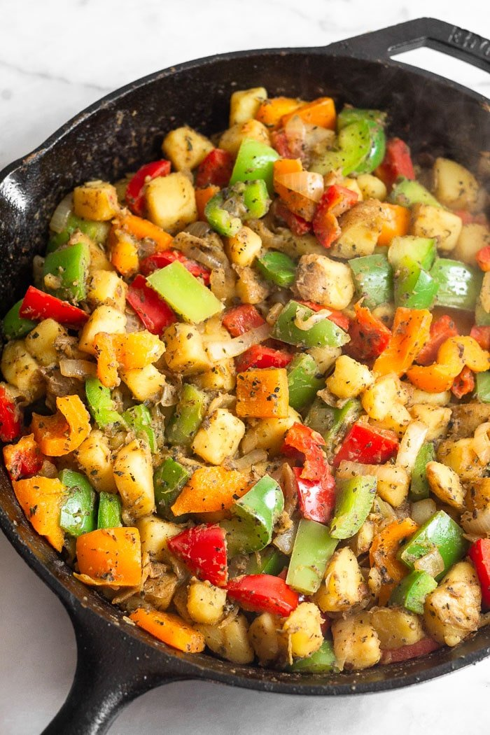 Cast iron skillet with with diced potatoes and peppers and seasoning.