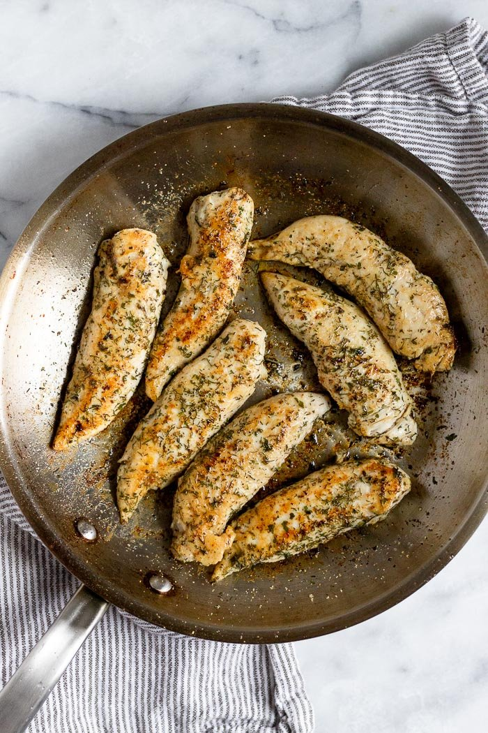 Pan with pan fried chicken tenders in it.