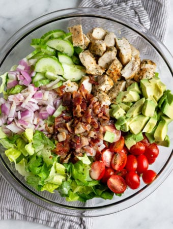 Large glass bowl filled with chopped chicken bacon ranch ranch salad.