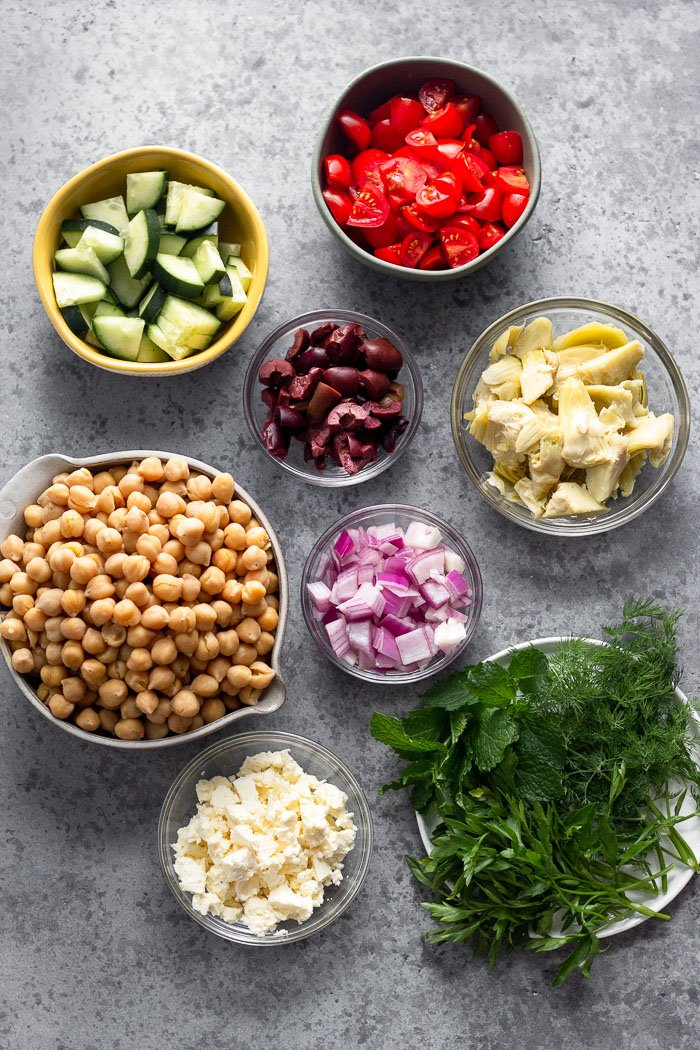 Grey counter filled with bowls of chickpeas, diced cucumbers, diced tomatoes, artichokes, diced red onion, diced olives, feta, and a plate of fresh herbs.