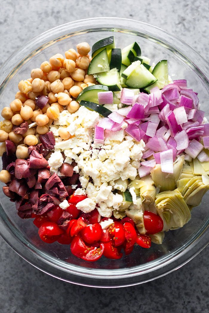 Large glass bowl filled with chickpeas, cucumbers, red onion, artichokes, tomatoes, Kalamata olives, and feta.