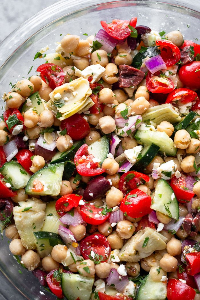Glass bowl filled with Mediterranean chickpea salad dressed with greek salad dressing and fresh herbs.