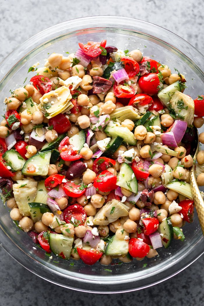 Overhead shot of easy greek chickpea salad with a spoon coming out of it.