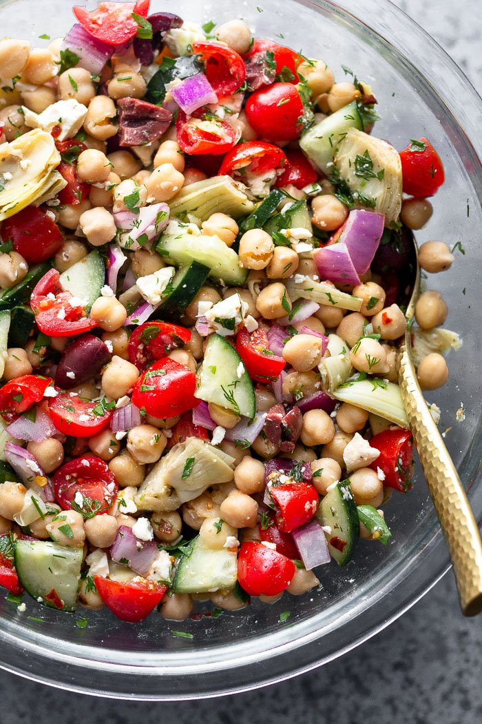 A large glass bowl filled with chopped greek chickpea salad with fresh herbs and a gold spoon in the bowl.