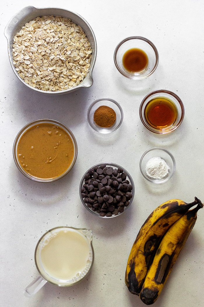 White counter top filled with individual bowls of rolled oats, vanilla extract, maple syrup, cinnamon, bananas, chocolate chips, baking soda, almond milk, and chocolate chips.
