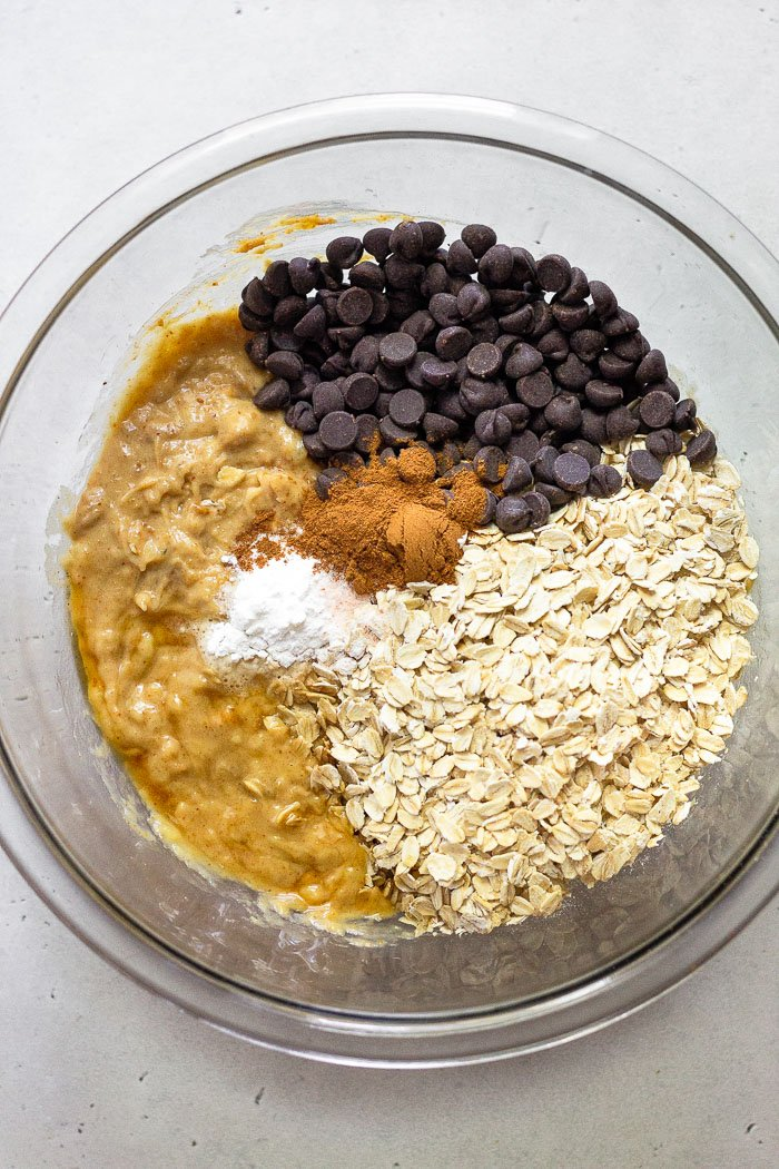 Large glass bowl of rolled oats, chocolate chips, spices, and mashed banana and peanut butter.