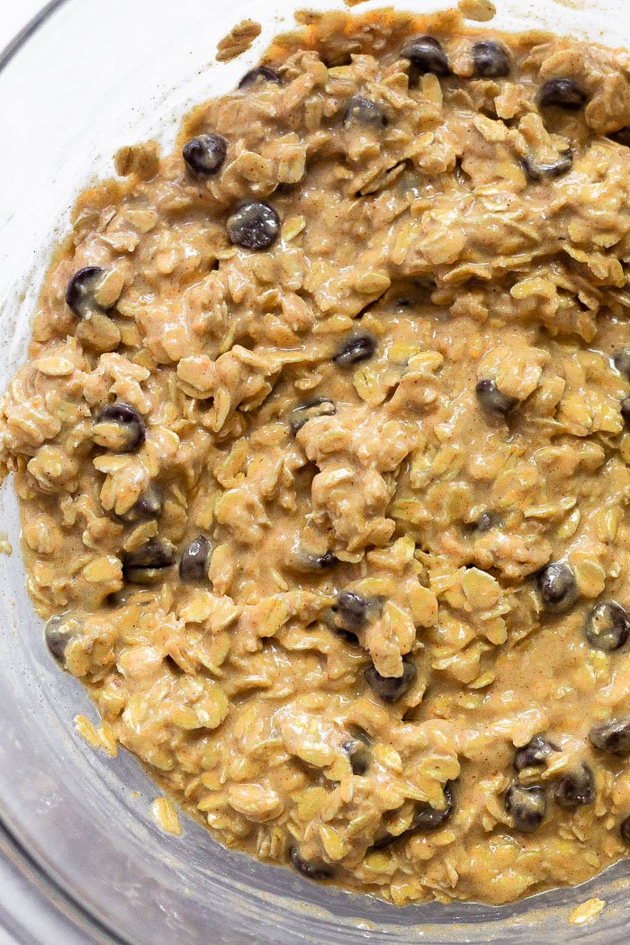 Large bowl of the mash bananas, peanut butter, oats, and chocolate chips mixed together.