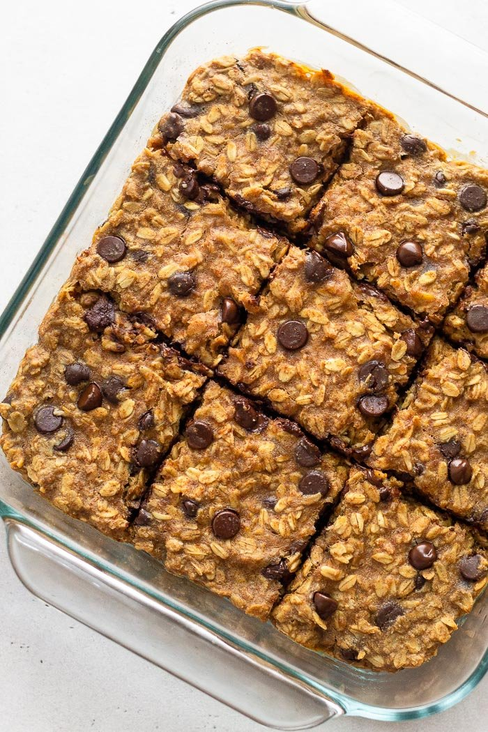 Chocolate peanut butter oatmeal bars in a glass baking pan on a white surface.