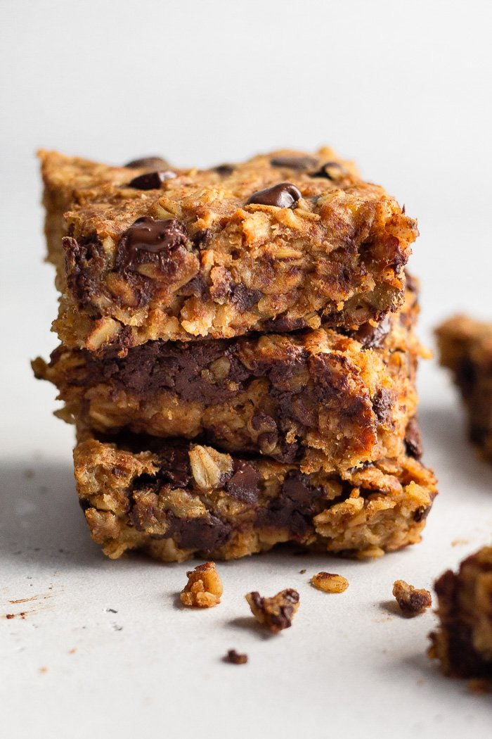 Three oatmeal chocolate chip bars stacked on top of each other with a few crumbs in front of them.