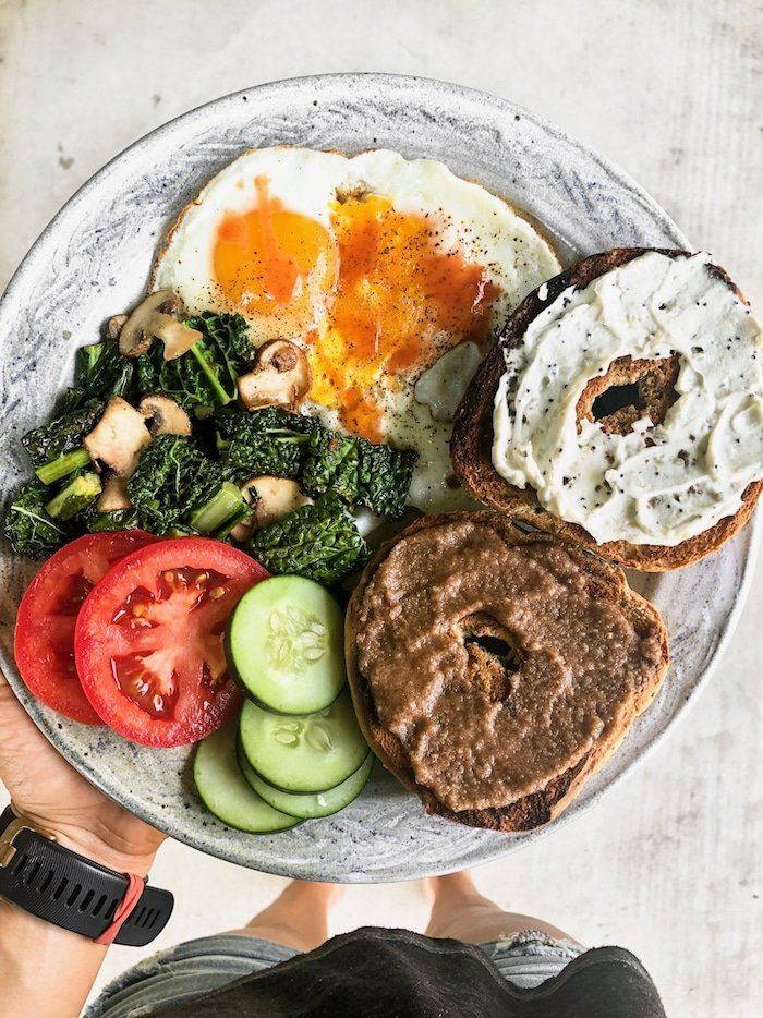 Plate of a 2 fried eggs, veggies, and a bagel with half with cream cheese and half with nut butter.