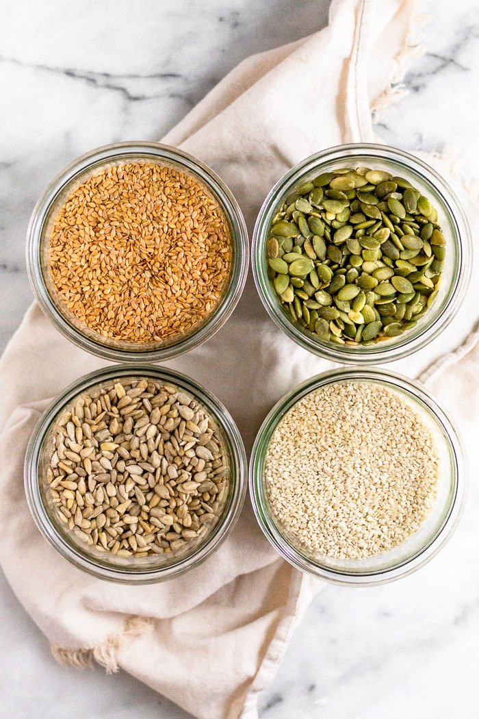 Four jars with different seeds in the (flax, pumpkin, sesame, and sunflower) for seed cycling to get your period back naturally.