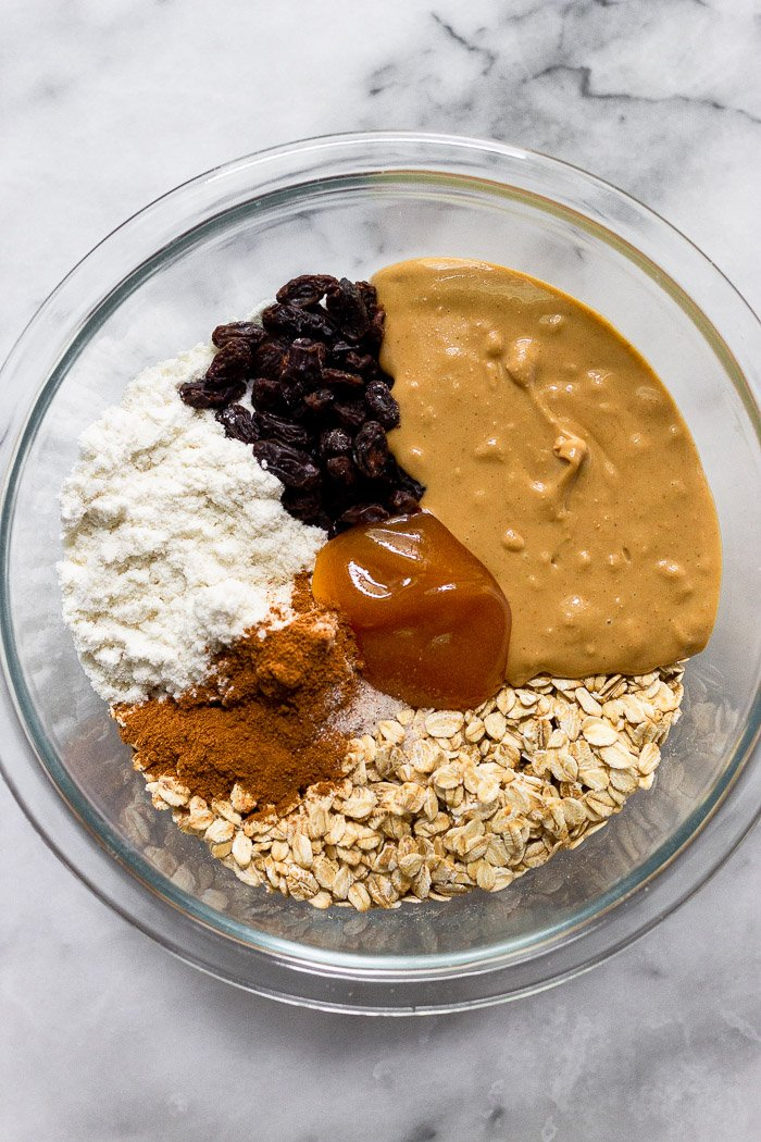Glass bowl of oats, cashew butter, raisins, protein powder, cinnamon, and honey.