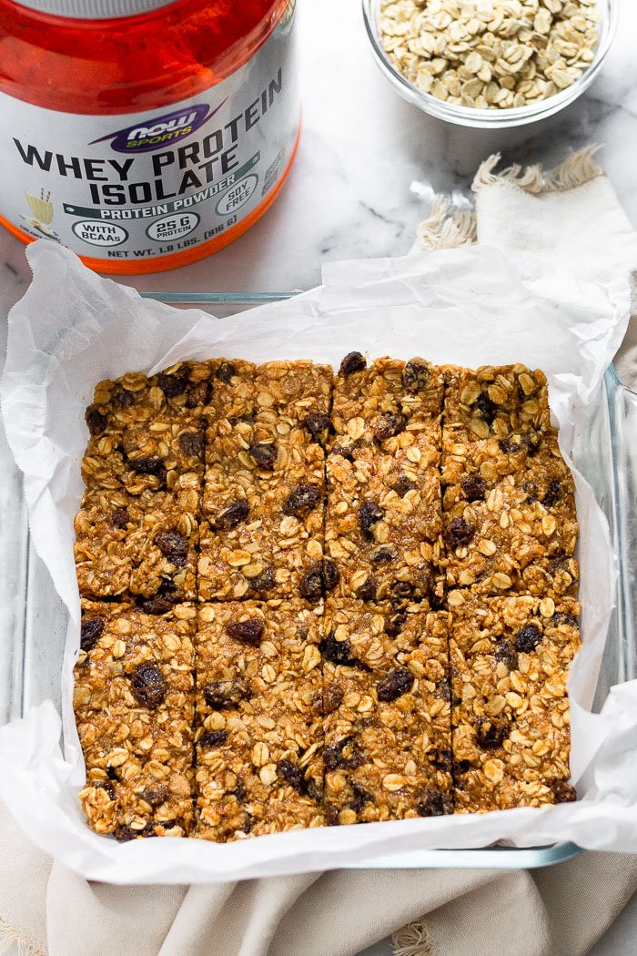 Glass baking dish filled with oatmeal raisin protein bars with a container of whey and a bowl of bowls behind it.