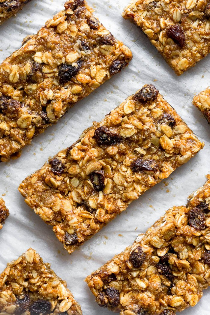 Overhead shot of oatmeal raisin bars lined up on a piece of parchment paper.