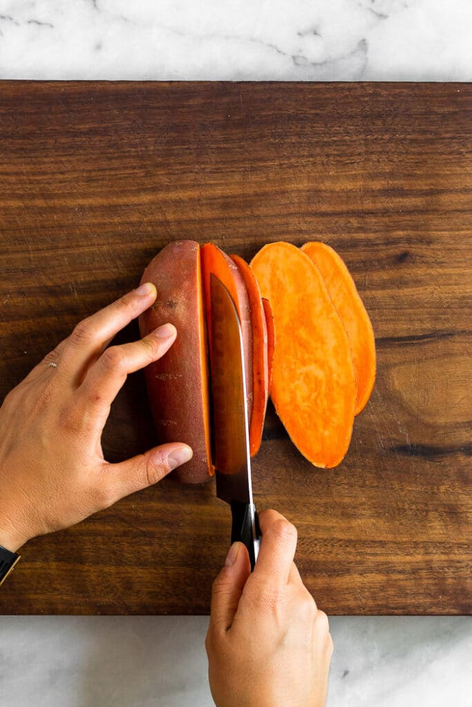 Overhead shot of someone cutting a sweet potato lengthwise