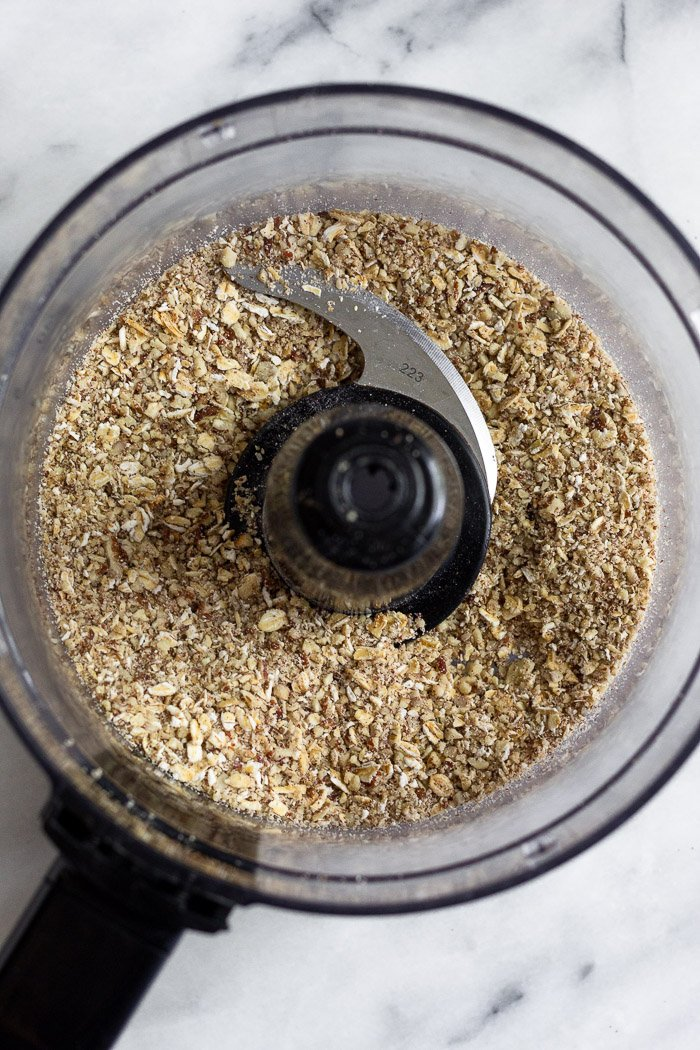 Food processor with sound up pecans and oats in it.