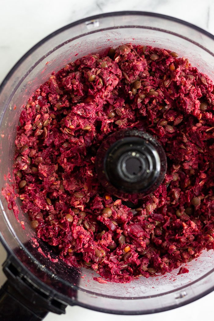 Food processor with beet lentil burger mixture in it.