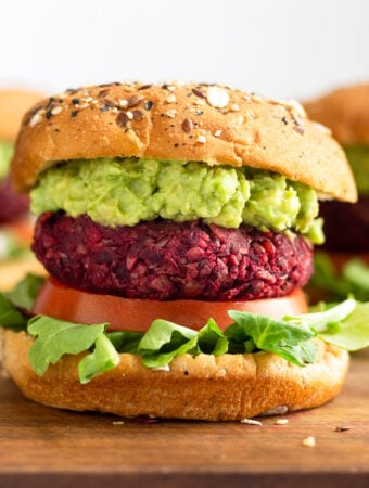 Close up of a beet burger on a bun with lettuce, tomato, and mashed avocado.