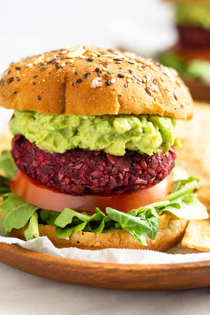 Close up of a beet burger with lettuce, tomato, and avocado. It is on a wooden plate with another burger in the distance behind it.